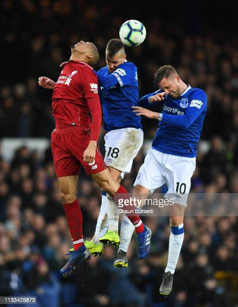 Fabinho of Liverpool jumps for the ball with Morgan Schneiderlin and Gylfi Sigurdsson of Everton during the Premier League match between Everton FC...