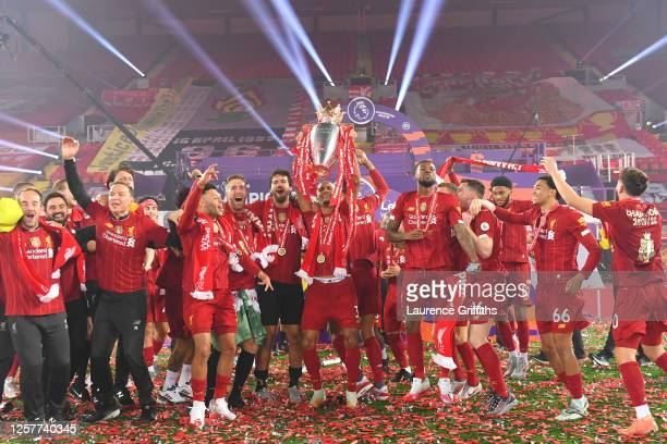 Fabinho of Liverpool leads the celebrations holding the trophy aloft as they celebrate winning the Title during the presentation ceremony of the...