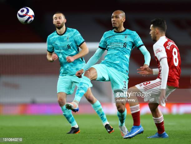Fabinho of Liverpool passes the ball under pressure from Dani Ceballos of Arsenal during the Premier League match between Arsenal and Liverpool at...