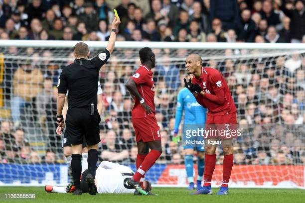 Fabinho of Liverpool recievs the yellow card during the Premier League match between Fulham FC and Liverpool FC at Craven Cottage on March 17 2019 in...