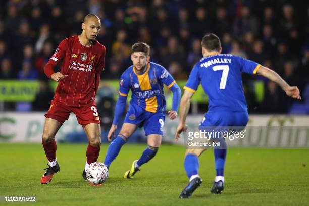 Fabinho of Liverpool runs with the ball under pressure from Callum Lang and Shaun Whalley of Shrewsbury Town during the FA Cup Fourth Round match...