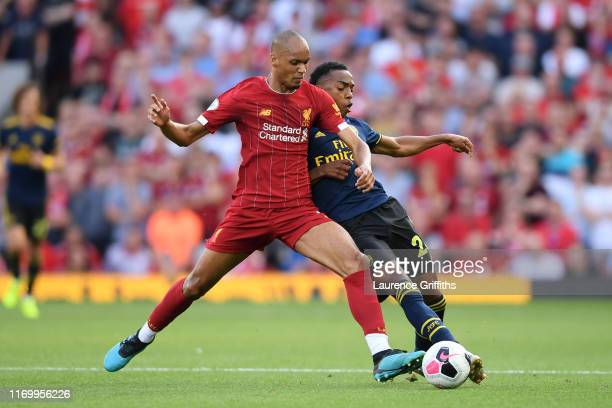 Fabinho of Liverpool tackles Joe Willock of Arsenal during the Premier League match between Liverpool FC and Arsenal FC at Anfield on August 24 2019...