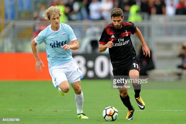 Fabio Borini of AC Milan compete for the ball with Dusan Basta of SS Lazio during the Serie A match between SS Lazio and AC Milan at Stadio Olimpico...