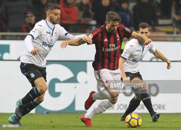 Fabio Borini of AC Milan is challenged by Leonardo Spinazzola of Atalanta BC during the serie A match between AC Milan and Atalanta BC at Stadio...