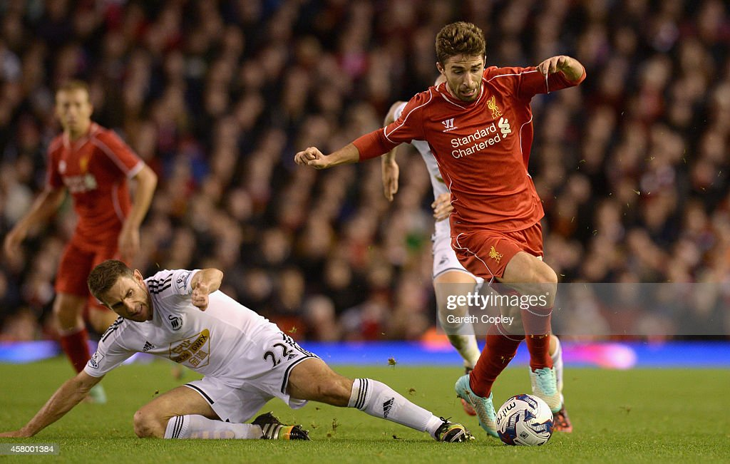 Fabio Borini of Liverpool is tackled by Angel Rangel of Swansea during the Capital One Cup Fourth Round match between Liverpool and Swansea City at Anfield on October 28, 2014 in Liverpool, England.
