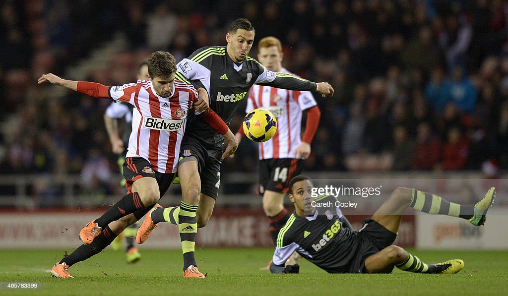 Fabio Borini of Sunderland is held back by Geoff Cameron of Stoke City during the Premier League match between Sunderland and Stoke City at Stadium of Light on January 29, 2014 in Sunderland, England.