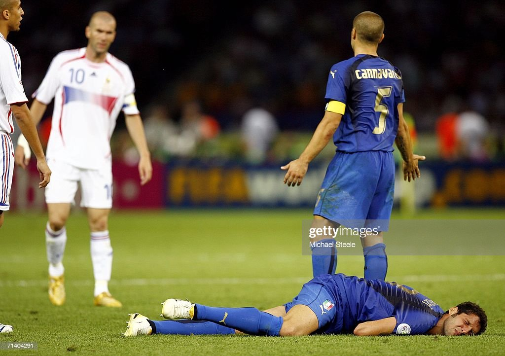 Fabio Cannavaro (R) of Italy gestures towards Zinedine Zidane #10 (L) of France, whilst Marco Materazzi of Italy lies injured, after being headbutted in the chest by Zinedine Zidane of France during the FIFA World Cup Germany 2006 Final match between Italy and France at the Olympic Stadium on July 9, 2006 in Berlin, Germany.