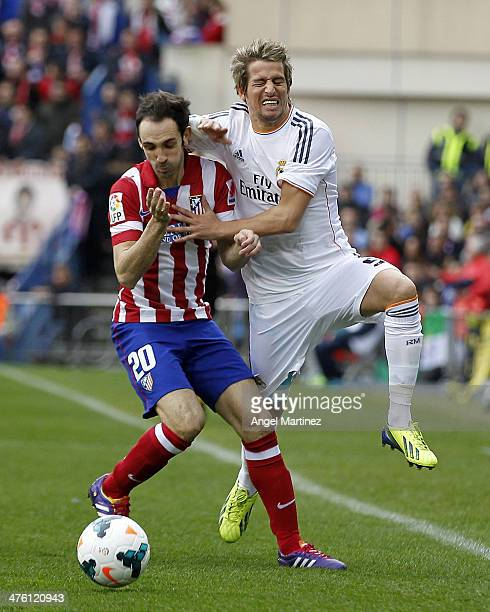 Fabio Coentrao of Real Madrid competes for the ball with Juanfran Torres of Atletico de Madrid during the La Liga match between Atletico de Madrid...