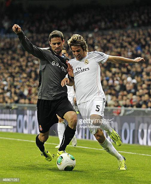Fabio Coentrao of Real Madrid competes for the ball with Raul Rodriguez of Espanyol during the Copa del Rey Quarter Final second leg match between...