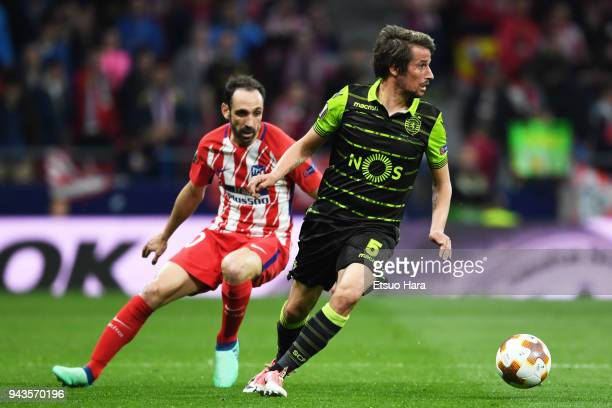 Fabio Coentrao of Sporting controls the ball under pressure of Juanfran of Atletico Madrid during the UEFA Europa League quarter final leg one match...
