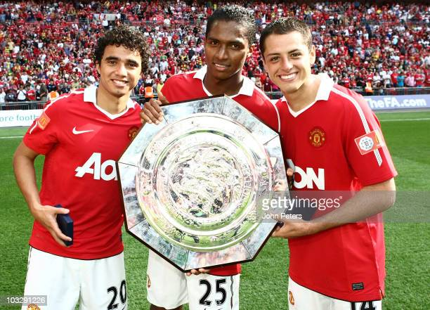 Fabio Da Silva Antonio Valencia and Javier Chicharito Hernandez of Manchester United pose with the Community Shield after the FA Community Shield...