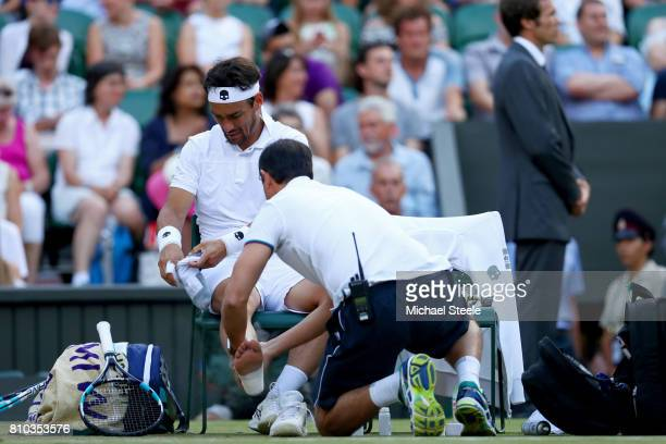 Fabio Fognini of Italy is given assistance during the Gentlemen's Singles third round match against Andy Murray of Great Britain on day five of the...