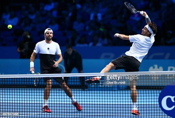 Fabio Fognini of Italy jumps for a forehand partnering Simone Bolelli of Italy in their men's doubles match against Rohan Bopanna of India and Florin...