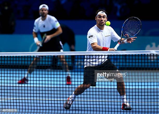 Fabio Fognini of Italy plays a backhand partnering Simone Bolelli of Italy in their men's doubles match against Bob Bryan and Mike Bryan of the...