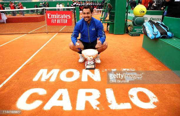 Fabio Fognini of Italy poses for a photograph with his winners trophy and the Monte Carlo court logo after his straight sets victory against Dusan...