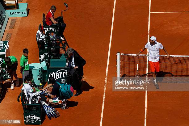 Fabio Fognini of Italy receives treatment from ATP physiotherapist Hugo Gravil as chair umpire Louise Engzell and Albert Montanes of Spain look on...