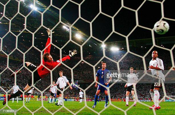 Fabio Grosso of Italy scores his team's first goal in extra time past the dive of Jens Lehmann of Germany during the FIFA World Cup Germany 2006...