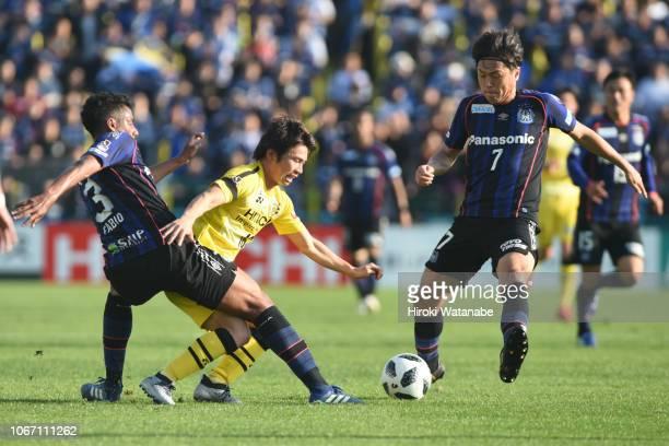 Fabio of Gamba Osaka and Yusuke Segawa of Kashiwa Reysol and Yasuhito Endo of Gamba Osaka compete for the ball during the JLeague J1 match between...