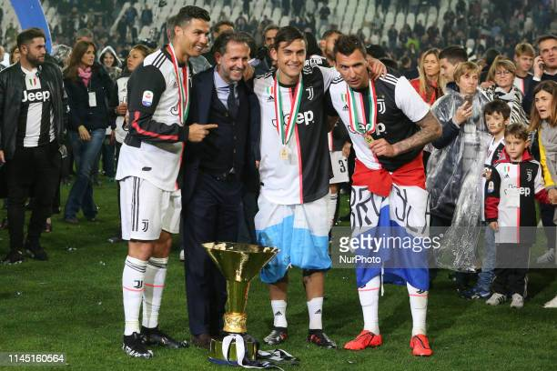 Fabio Paratici Cristiano Ronaldo Paulo Dybala and Mario Mandzukic of Juventus FC with the trophy of Scudetto during the victory ceremony following...