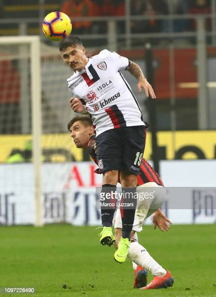 Fabio Pisacane of Cagliari Calcio lcompetes for the ball with Krzysztof Piatek of AC Milan during the Serie A match between AC Milan and Cagliari at...