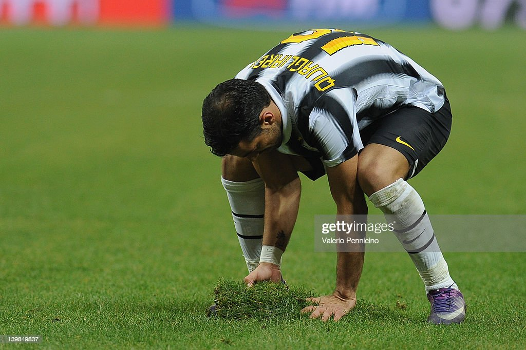 Fabio Quagliarella of Juventus FC attempts to mend the pitch by replacing a piece of turf that has come loose during the Serie A match between AC Milan and Juventus FC at Stadio Giuseppe Meazza on February 25, 2012 in Milan, Italy.