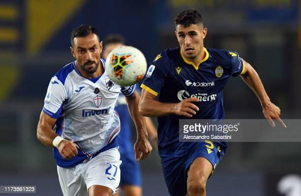 Fabio Quagliarella of UC Sampdoria competes for the ball with Davide Faraoni of Hellas Verona during the Serie A match between Hellas Verona and UC...