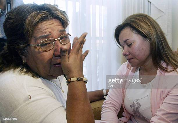 Fabiola Perdomo the wife of deputy Juan Carlos Narvaez one of the 11 congressmen killed in captivity weeps next to Maria del Carmen Acuria after...