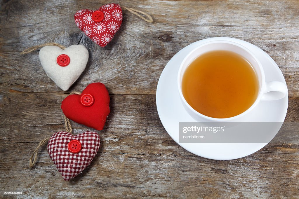 Fabric hearts and cup of tea on wooden background : Stock Photo