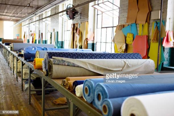 fabric rolls on table in factory - fábrica têxtil imagens e fotografias de stock