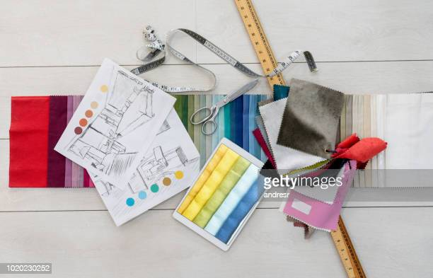 fabric swatches and tailoring tools on the table of a textile shop - fashion industry stock pictures, royalty-free photos & images