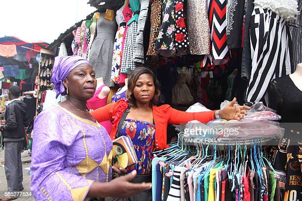A fabric vendor attends to a client at the SemePodji market the border town between Benin and Nigeria on August 2 2016 Benin President Patrick Talon...