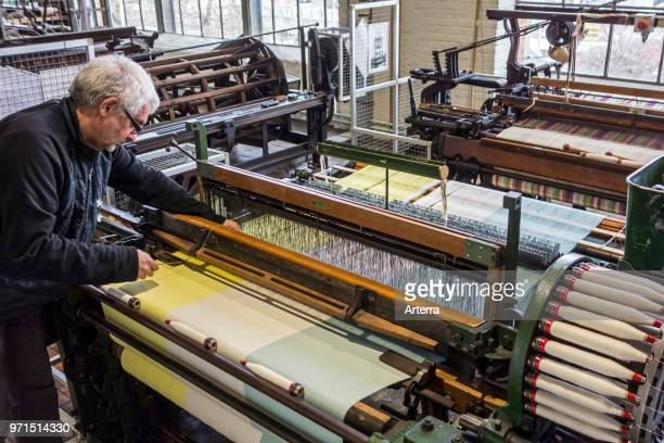 Fabric weaver operating mechanical flying shuttle loom / shuttle weaving machine in cotton mill / spinningmill