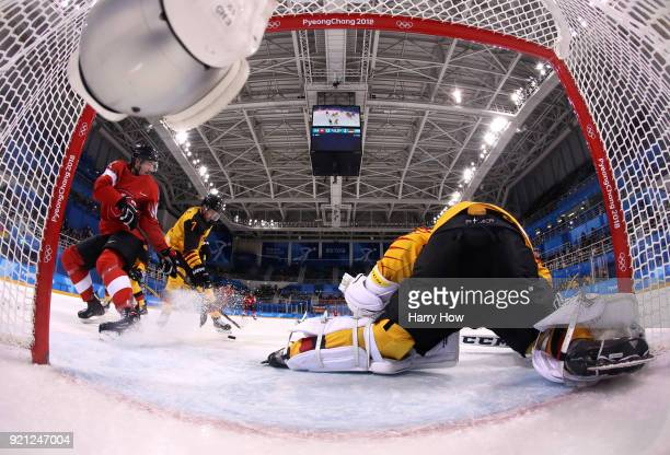 Fabrice Herzog of Switzerland attempts a shot against Daryl Boyle and Danny Aus Den Birken of Germany in the first period during the Men's Ice Hockey...