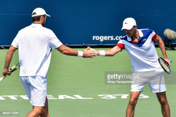 Fabrice Martin and teammate Edouard Roger-Vasselin of France encourage one another in their doubles match against Raven Klaasen of Russia and Rajeev...