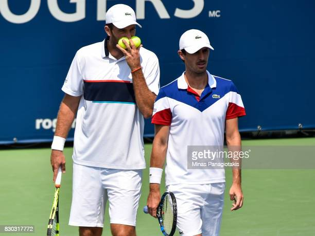 Fabrice Martin and teammate Edouard RogerVasselin of France talk over their strategy in their doubles match against Raven Klaasen of Russia and...