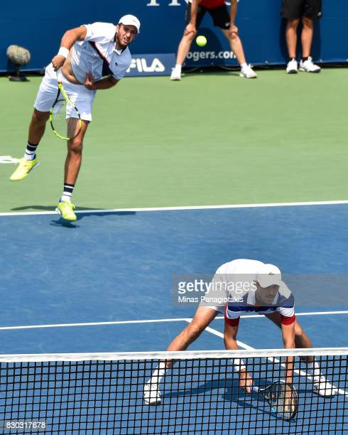 Fabrice Martin of France serves as teammate Edouard Roger-Vasselin ducks down in their doubles match against Raven Klaasen of Russia and Rajeev Ram...