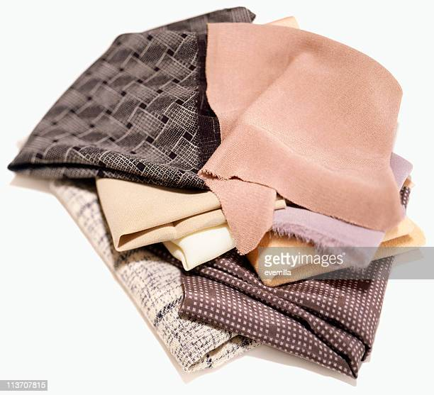fabrics in a pile cut out on white