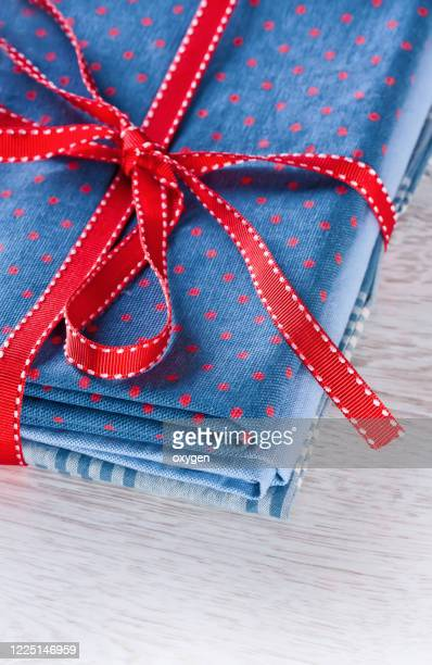 fabrics pile, dark blue with red polka dots pattern, red ribon on table background - ribbon sewing item stock pictures, royalty-free photos & images