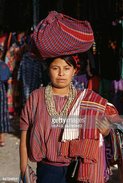 Fabricseller wearing traditional clothing with a basket on her head Solola market Guatemala