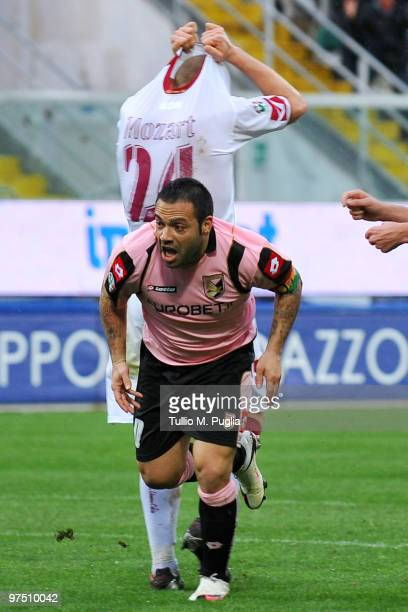 Fabrizio Miccoli of Palermo celebrates after scoring as Mozart of Livorno shows his dejection during the Serie A match between US Citta di Palermo...