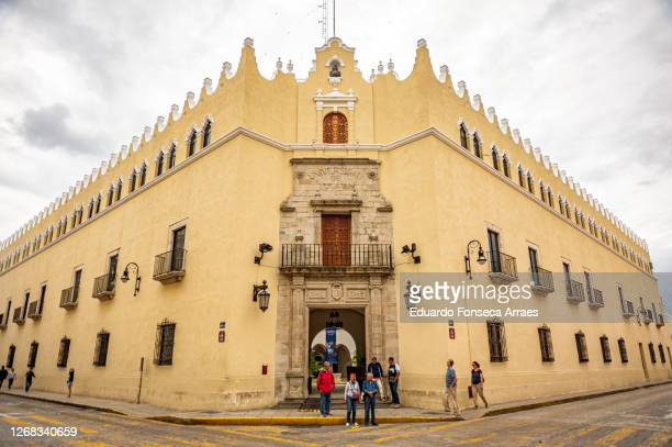facade and entrance of the autonomous university of yucatan (universidad autónoma de yucatán), an old spanish colonial style building, against an overcast sky - universidad stock pictures, royalty-free photos & images