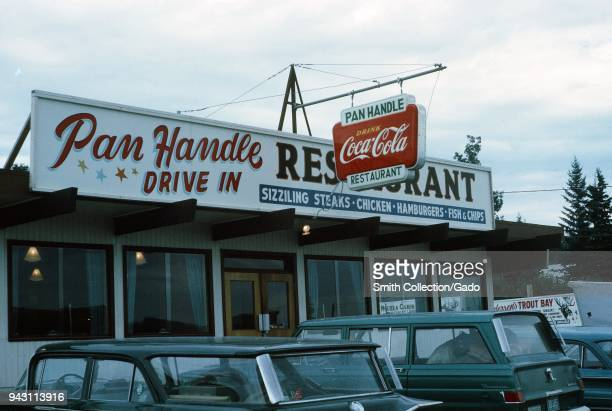 Facade of a classic American drive in restaurant the Pan Handle Drive In with cars parked outside and a sign for Coca Cola visible United States 1965