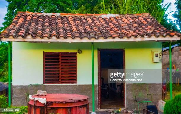 Facade of a Cuban peasant's house in the Hanabanilla area The simple house is covered with clay tiles roof and has a water reservoir tank on the front