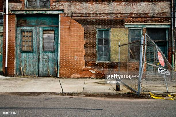 facade of a grungy abandoned urban warehouse - abandoned stock pictures, royalty-free photos & images