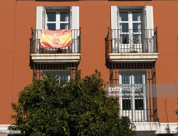 facade of a house in sevilla with spanish flags on the balconies. - capital cities stock pictures, royalty-free photos & images