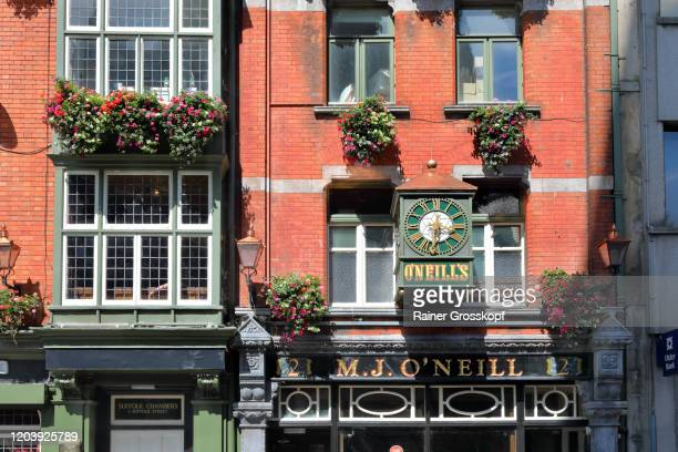 facade of an irish pub decorated with flowers in church lane - rainer grosskopf stock pictures, royalty-free photos & images