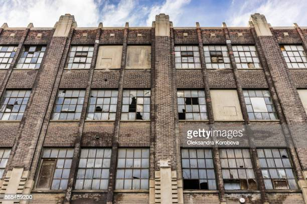 Facade of an old brick industry building with broken windows.