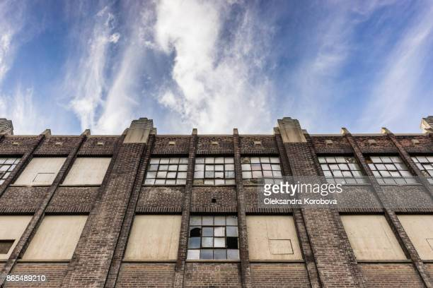 facade of an old brick industry building with broken windows. - abandoned stock pictures, royalty-free photos & images