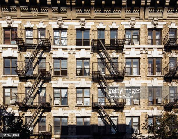 Facade of an old residential building with fire escape ladders in Brooklyn, New York City, USA