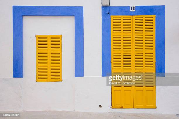 Facade of blue and white house with yellow shutters in the old town.